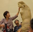 複製ヴィーナス像の唇にふれる視覚障害のある参加者