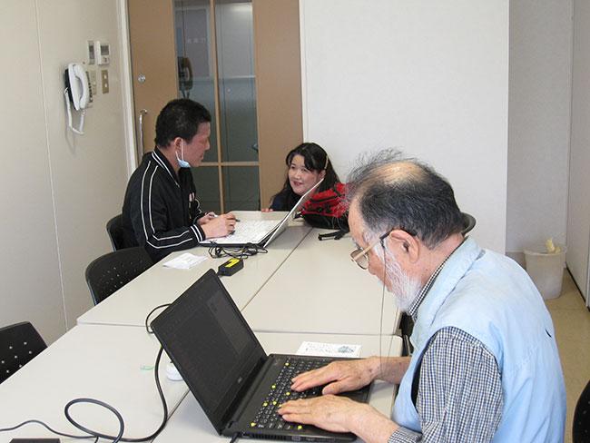 パソコン操作する利用者さんと職員
