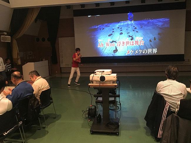 スクリーンの前で熱唱する参加者