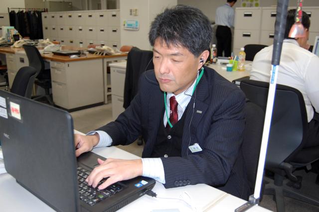 デスクでパソコンに向かいデータ作成中の岡田さん