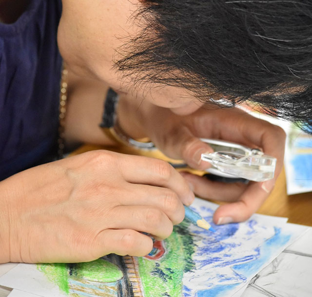 画用紙に顔を近づけルーペを用いて色鉛筆で青空を描く