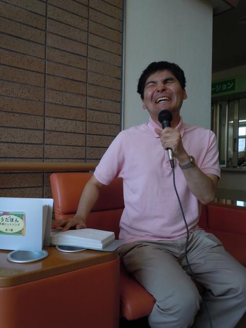 写真:点字を読みながらカラオケを歌う男性