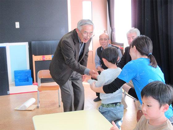 石津さんと握手する子どもたち