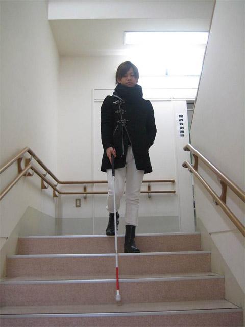 白杖を利用して階段を降りる濱ノ上さん