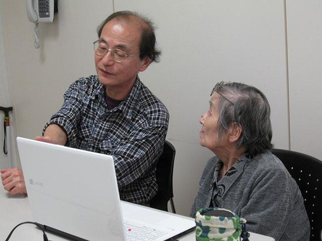 パソコン訓練の時間 ボランティアさんのお話を一生懸命に聞く利用者さん