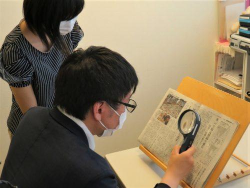 ルーペを使って新聞を読んでいます