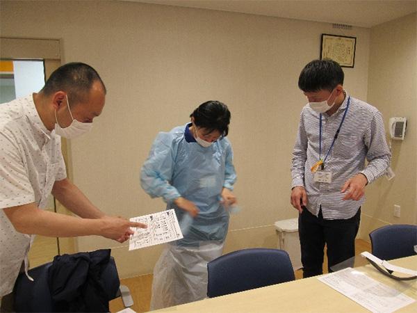 マニュアルに則しながらエプロンを付ける手順を確認し合う職員スタッフ