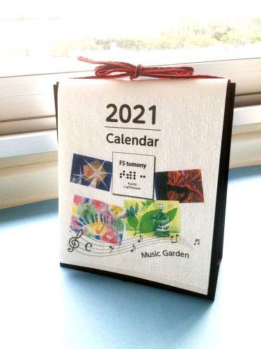 カレンダーの表紙。黒い台紙に乗せ、赤い紐をリボン結びにしてアクセントにしています。