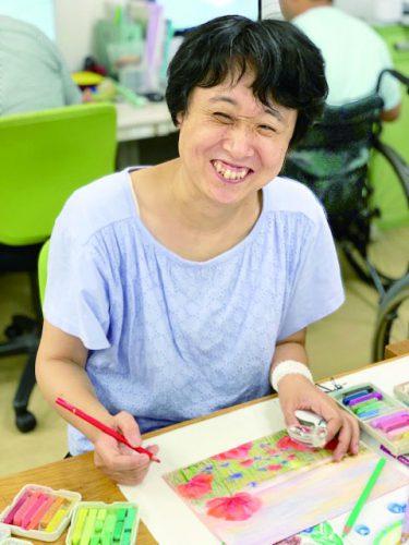 ルーペを左手に、色鉛筆を右手に持ち、作画中の山崎佳子さん。