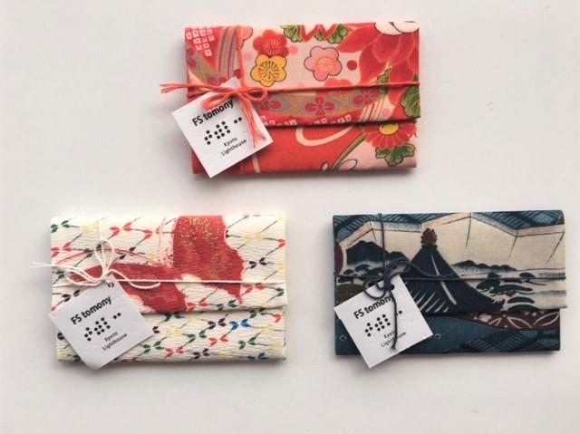 が3点(赤系、白地に蝶の柄、白黒の柄)のカードケース。紐で十字に結び、ブランドタグを飾り付けた脱プラスチックのパッケージを施しています。