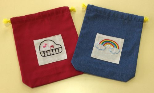 刺繍入りの巾着袋( 左:ピアノの刺繍の赤い巾着袋 右:虹の刺繍の青い巾着袋
