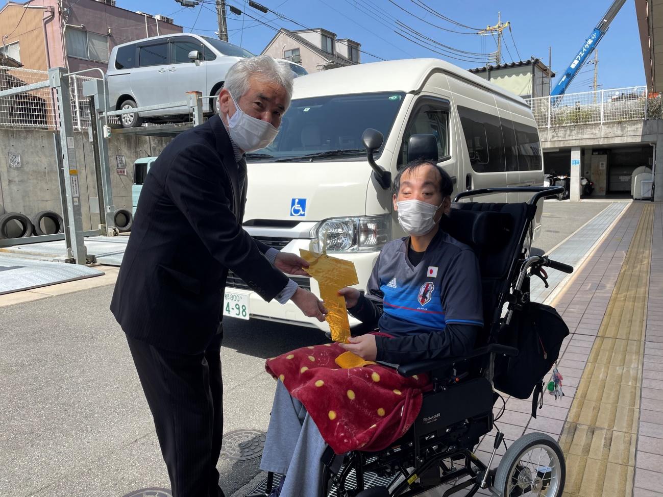 ハイエースをバックに田中様から瀧本理事長へレプリカキーを手渡されています